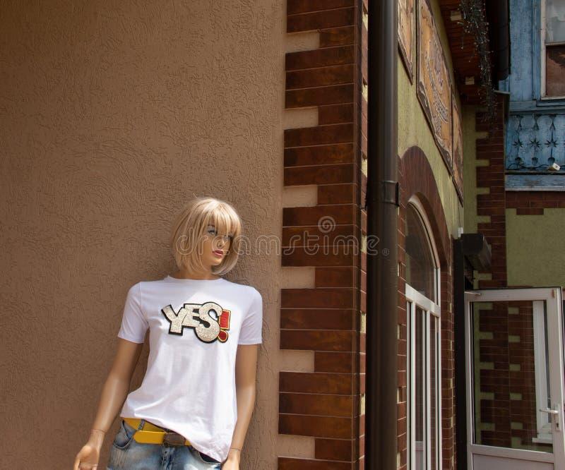 Пластиковая девушка ждет ее пластикового друга на угле улицы стоковые фотографии rf