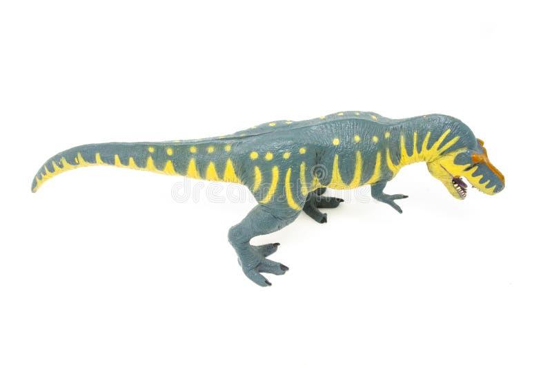 Пластиковая желтая голубая игрушка динозавра Rex тиранозавра над верхней частью стоковые фотографии rf