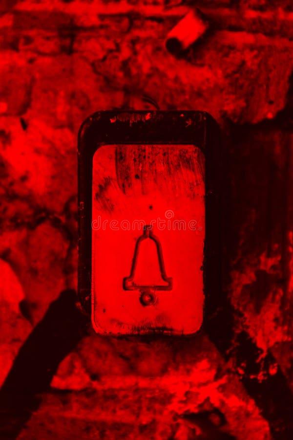 Пластиковая кнопка со значком колокола doorphone с трассировками повреждения и царапин прикрепленных в кирпичную стену Кнопочный  стоковая фотография rf
