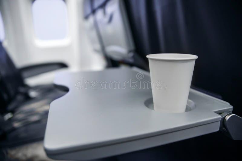 Пластиковая чашка на таблице в плоскости во время полета потребление алкоголя на борту стоковая фотография rf