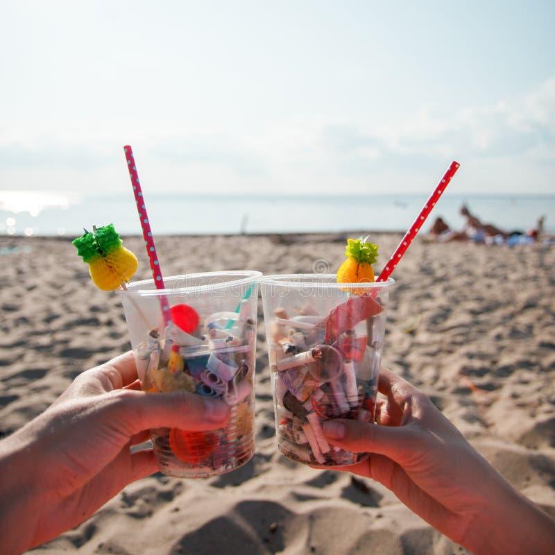 Пластиковое загрязнение в проблеме окружающей среды океана, руки держа пластиковые чашки с соломами и коктейлем от отброса пляжа  стоковое фото rf