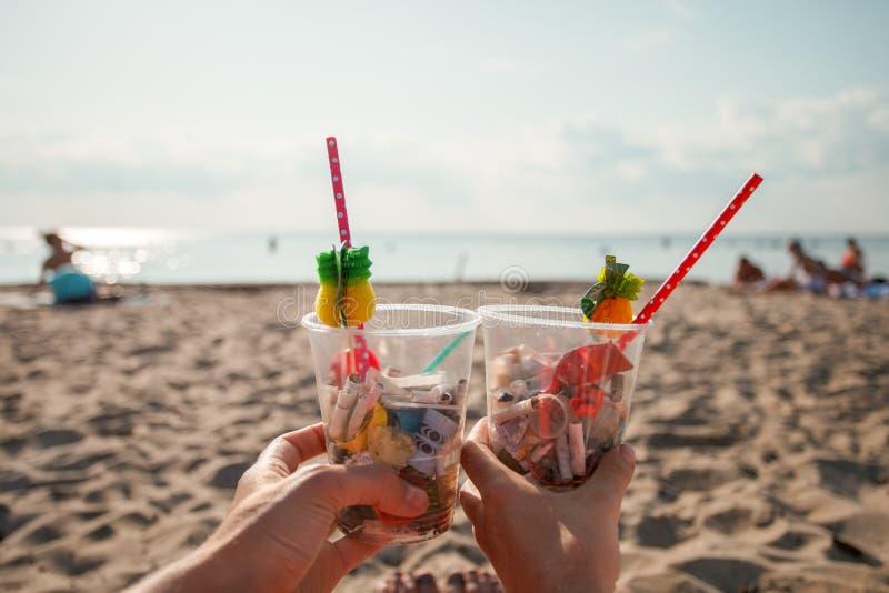 Пластиковое загрязнение в проблеме окружающей среды океана, руки девушек держа пластиковые чашки с соломами и коктейлем от отброс стоковое фото