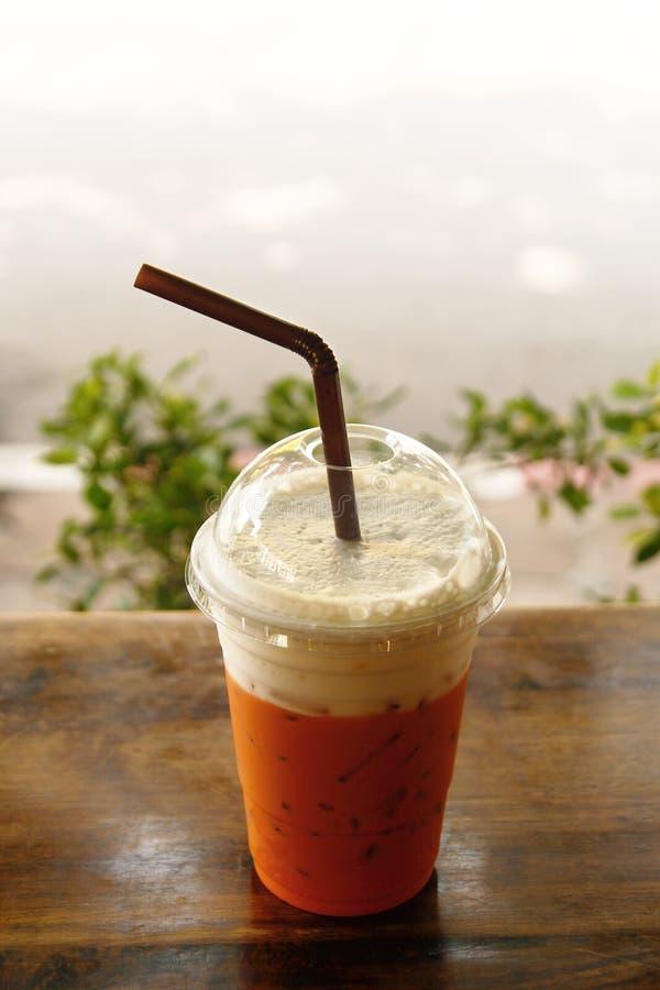 Пластиковое стекло с тайским холодным чаем молока на деревянном столе стоковые изображения rf