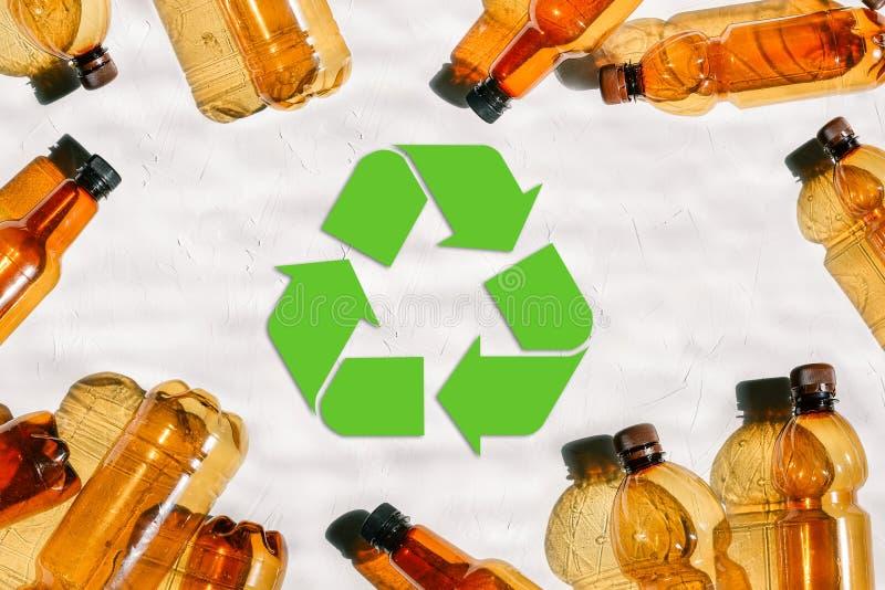 Пластиковые бутылки и метка повторного пользования Повторно использовать пластмассы r Зеленый цвет повторно использует символ env стоковое фото