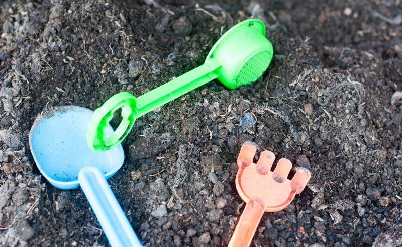 Пластиковые инструменты земледелия как борона и лопаткоулавливатель положили в черную почву готовую к использованный для учить ре стоковая фотография rf