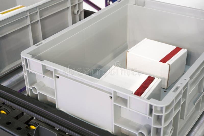 Пластиковые клети на роликах транспортера в продукции фабрики или хранении и сортировать склада стоковые изображения