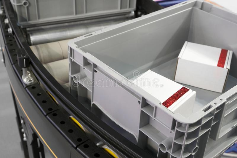 Пластиковые клети на роликах транспортера в продукции фабрики или хранении и сортировать склада стоковое изображение rf