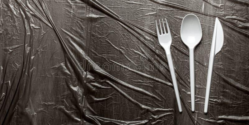 Пластиковые столовые, вилки, ложки и ножи Загрязнение окружающей среды пластиковыми и микропластмассами Черно-пластиковый фон стоковые изображения rf