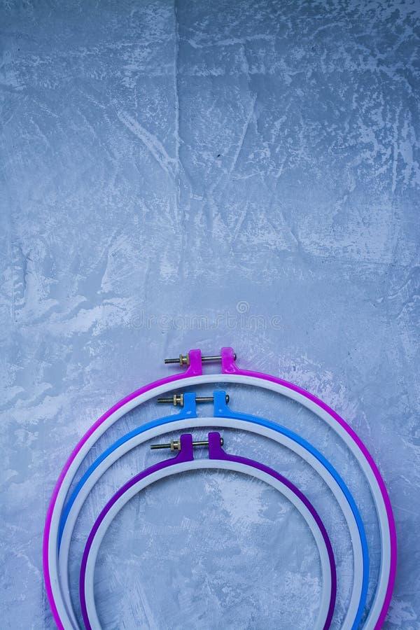 Пластиковый обруч на светлой предпосылке под бетоном 3 обруча пинк, голубой, пурпурный r Космос под текстом стоковая фотография rf