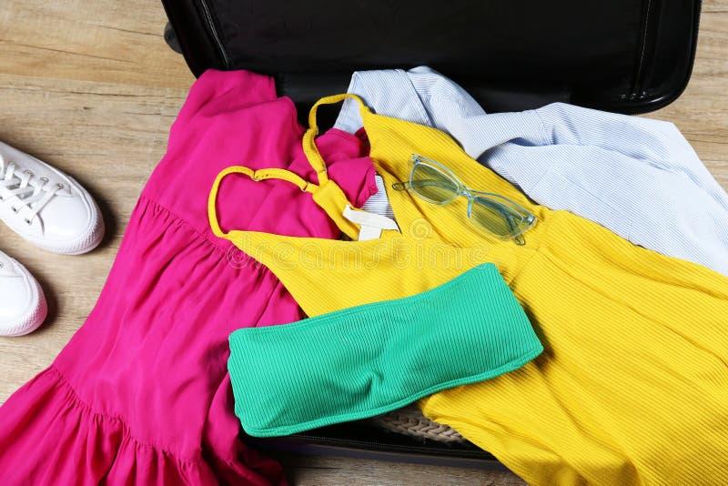 Пластиковый чемодан hardshell упакованный с деталями случайной одежды стоковое изображение