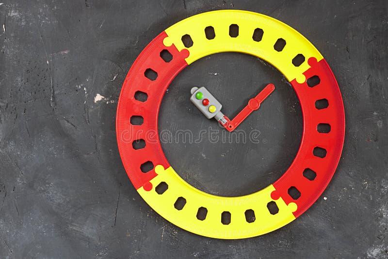 Пластиковый яркий круглый светофор дороги и игрушки как руки часов в центре на черной предпосылке доски с космосом экземпляра top стоковые фото