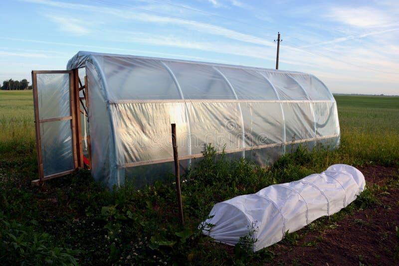 Пластичная оранжерея парника на поле в ферме стоковое изображение rf