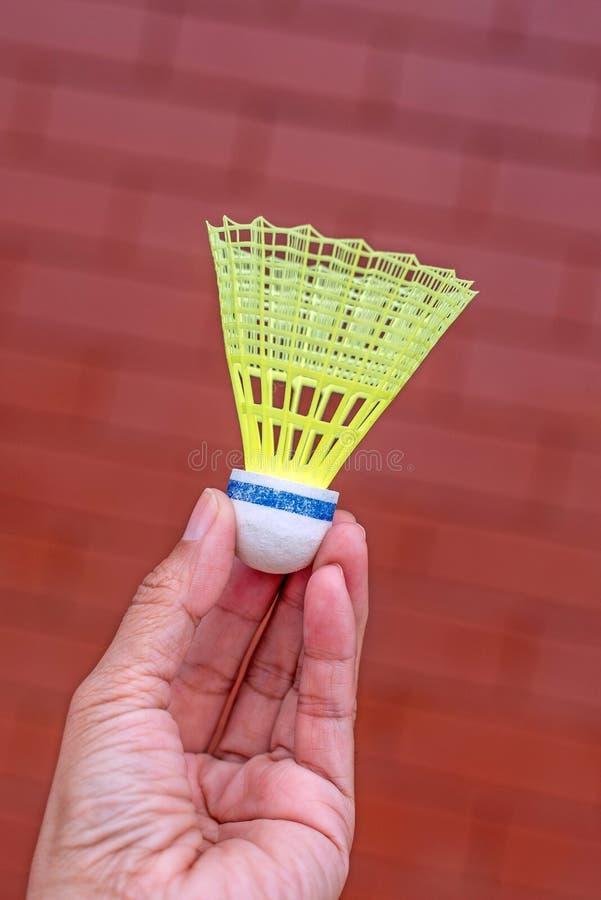 Пластичное shuttlecock бадминтона в руке стоковое изображение