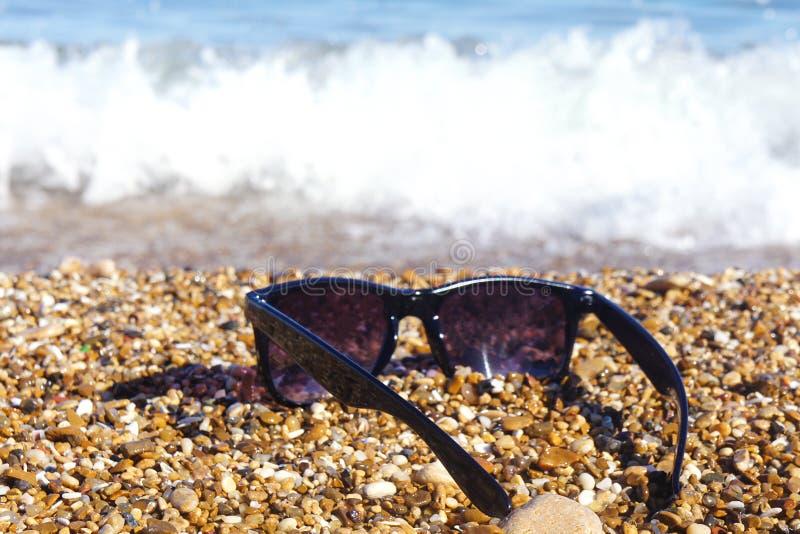 Пластичные солнечные очки на фоне камней моря Море на заднем плане стоковые фото