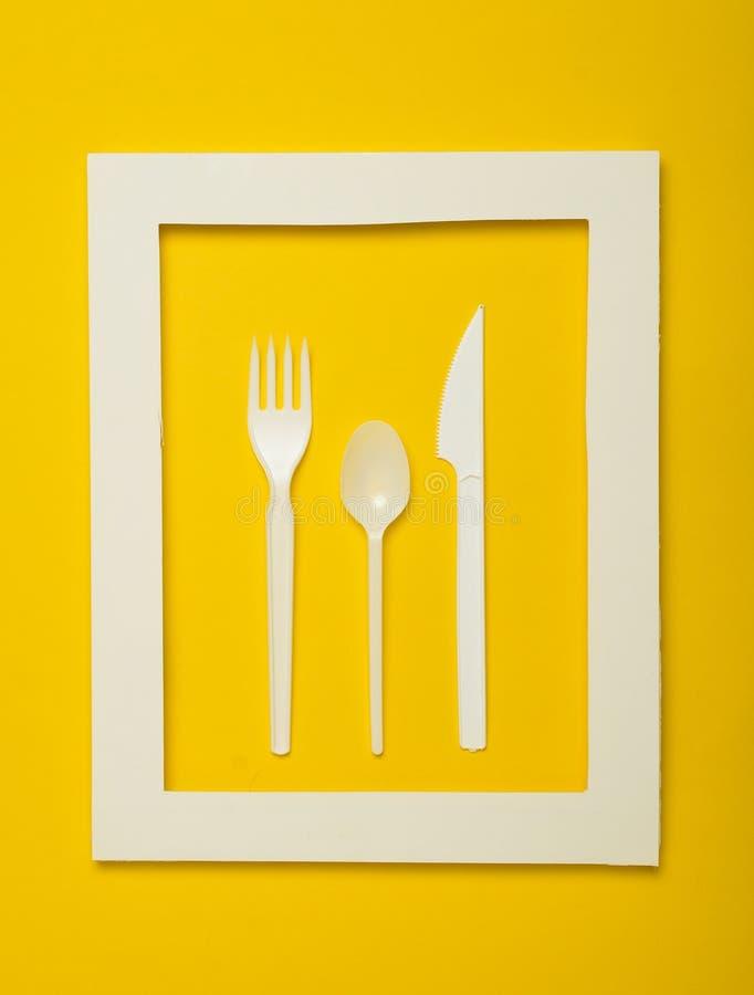 Пластичный столовый прибор для пикников в белой рамке на желтой предпосылке Устранимая ложка, вилка, нож Взгляд сверху, minimalis стоковое изображение