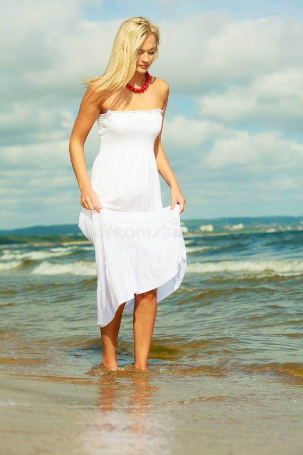 Платье белокурой женщины нося идя в воду стоковое фото