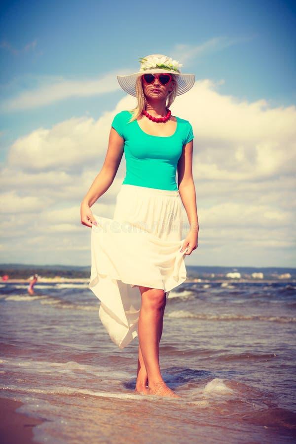 Платье белокурой женщины нося идя на пляж стоковое изображение rf