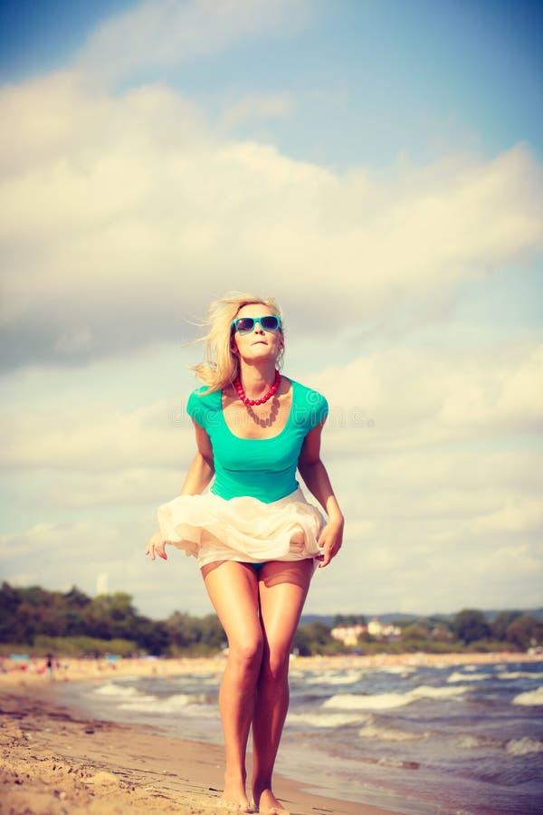 Платье белокурой женщины нося идя на пляж стоковые изображения rf