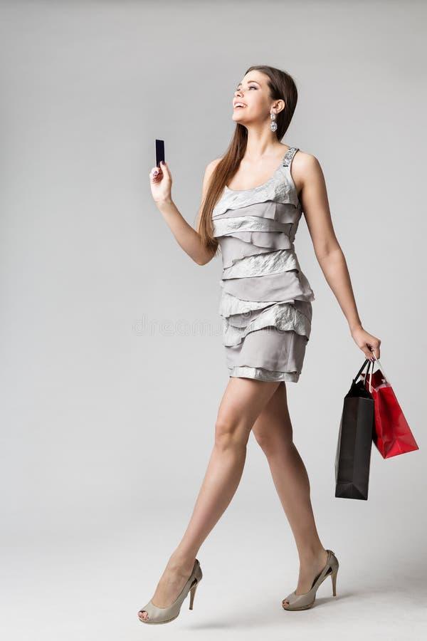 Платье женщины ходя по магазинам с кредитной карточкой и бумажные мешки, портрет студии фотомодели полнометражный, девушка идя ку стоковое фото rf