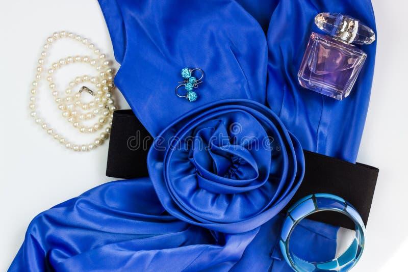 Платье и аксессуары ярких голубых женщин на белой предпосылке Пояс цветка, ожерелье жемчуга, серьги, браслет и духи стоковые фото