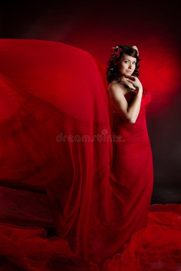 Платье красного цвета фотомодели развевая, женщина в порхая ткани летания стоковое изображение