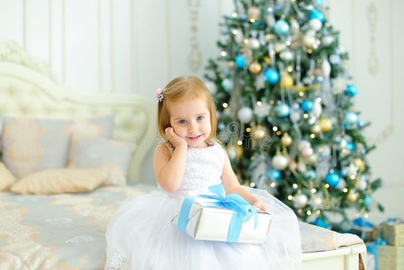 Платье маленькой кавказской девушки нося белое держа подарок близко украсило рождественскую елку в спальне стоковое фото