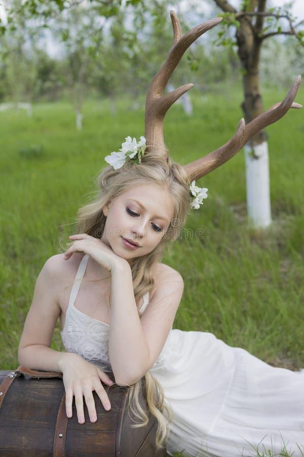 Платье предназначенной для подростков белокурой девушки нося белое с рожками оленей на ее голове стоковые изображения rf