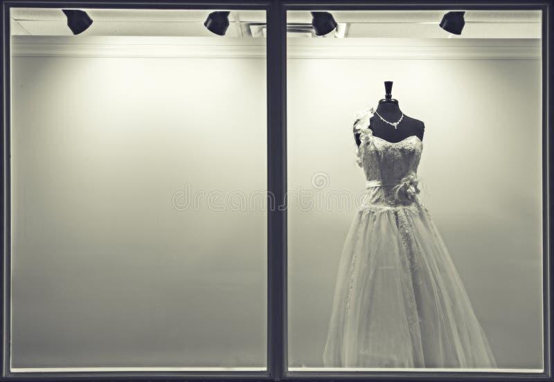 Платье свадьбы в окне магазина стоковое фото rf