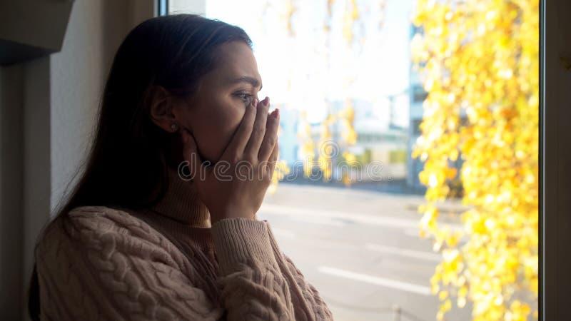 Плача дама смотря через окно, испуганное идти outdoors заболевание агорафобии стоковая фотография rf