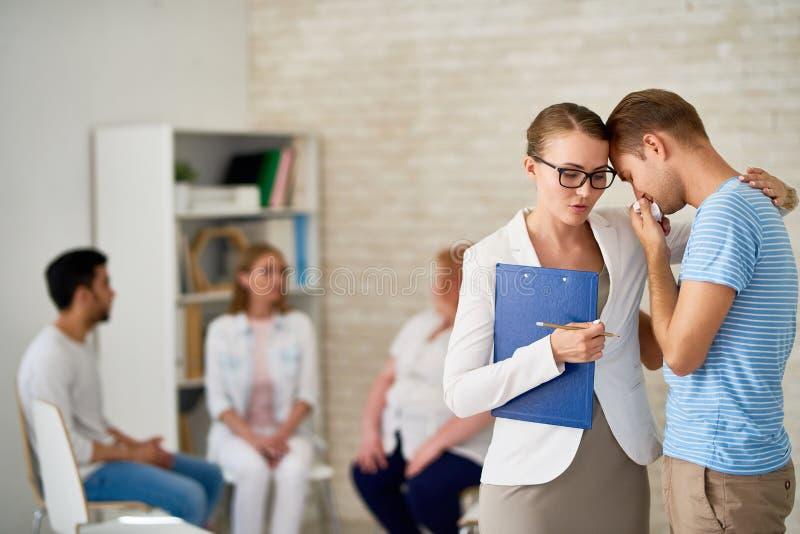 Плача молодой человек на терапевтической сессии группы стоковые изображения rf