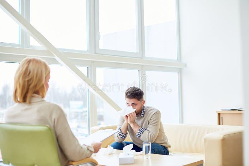 Плача человек на посещении с терапевтом стоковая фотография
