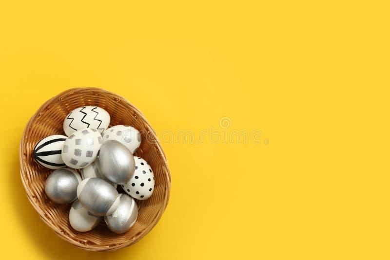Плетеная корзина вполне покрашенных пасхальных яя на предпосылке цвета, взгляде сверху стоковая фотография rf