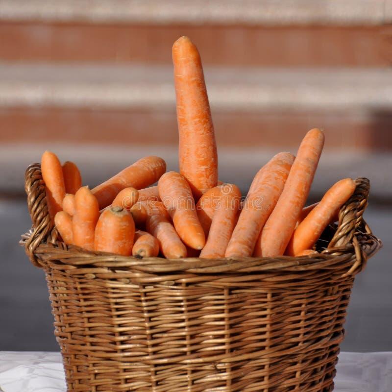 Плетеная корзина заполнила со свежими большими морковами стоковое изображение