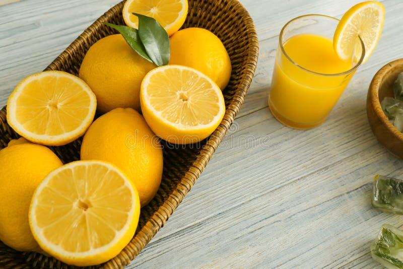 Плетеная корзина со зрелыми лимонами и стеклом свежего сока на деревянном столе стоковое изображение rf