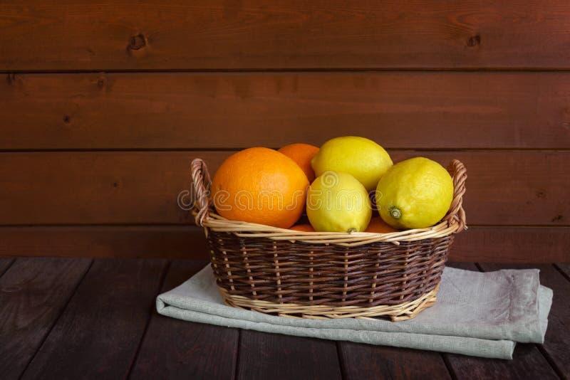 Плетеная корзина со свежими зрелыми апельсинами и лимонами на достигшем возраста деревянном столе стоковое фото rf