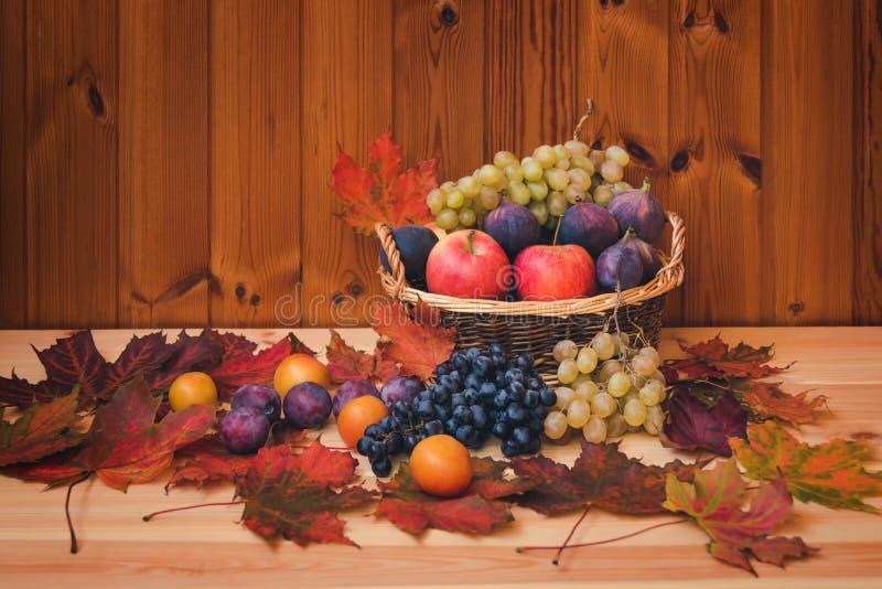 Плетеная корзина со свежими фруктами и кленовыми листами осени на деревянной предпосылке стоковая фотография rf