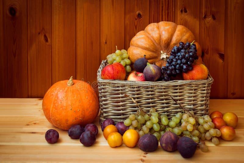 Плетеная корзина с тыквами и свежими фруктами на деревянном столе стоковое фото