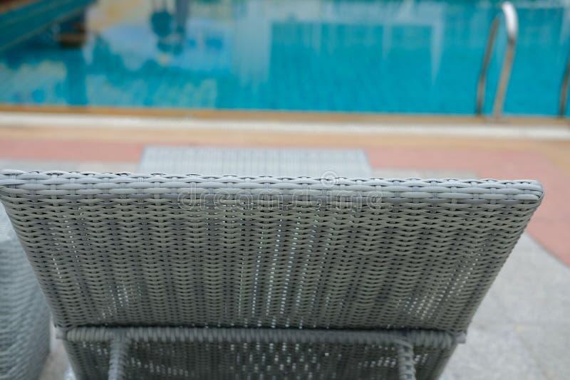 Плетеное deckchair шезлонга бассейна ротанга на бассейне стоковые изображения rf