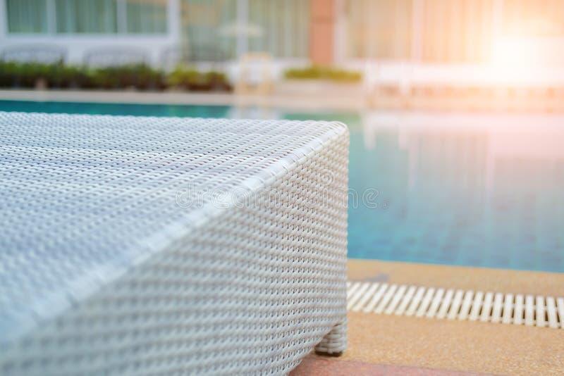 Плетеное deckchair шезлонга бассейна ротанга на бассейне стоковое фото rf