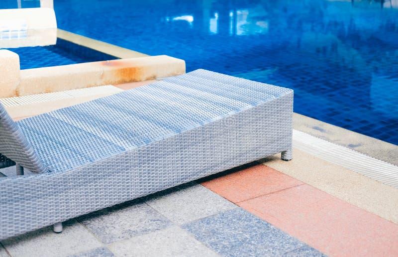 Плетеное deckchair шезлонга бассейна ротанга на бассейне стоковые фотографии rf