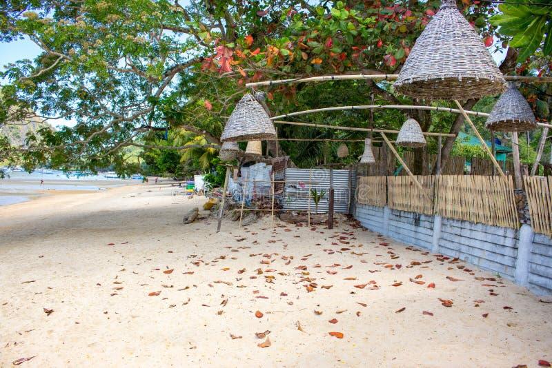 Плетеные лампы вися от деревьев на пляже, Филиппин Украшение на открытом воздухе фонариков на каникулах берега моря тропических стоковые фотографии rf
