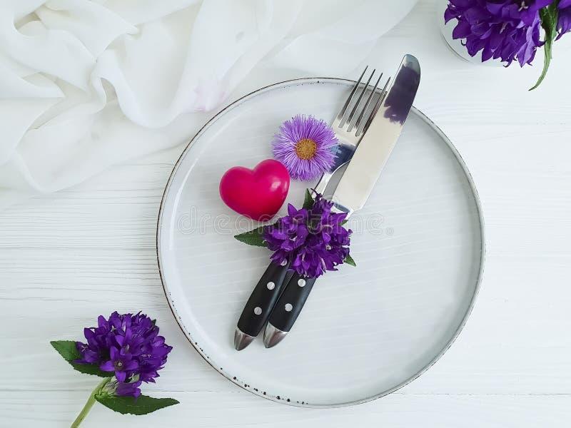 Плита, вилка, хризантема цветка ножа, год сбора винограда празднует красивый колокол приглашения, сердце на деревянной предпосылк стоковое изображение