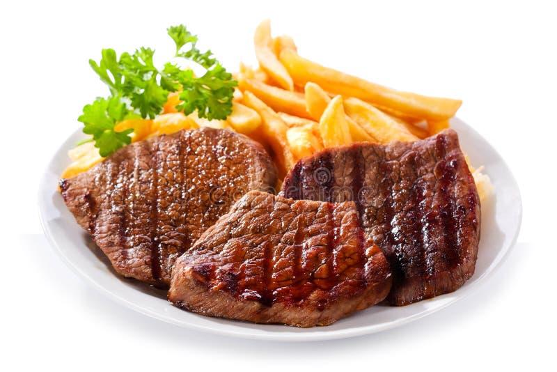 Плита зажженного мяса с fries стоковые фото