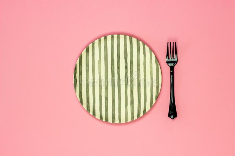 Плита и вилка на розовой предпосылке minimalism стоковое изображение
