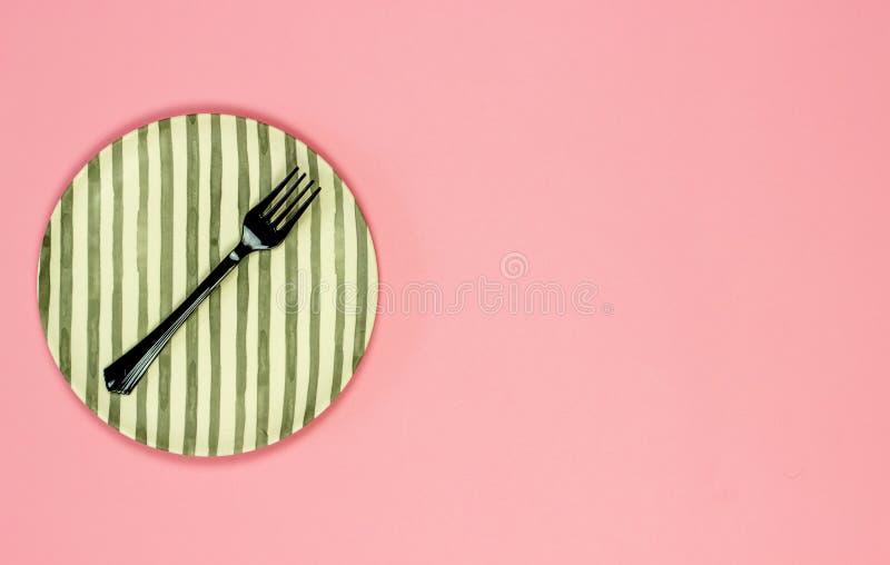 Плита и вилка на розовой предпосылке minimalism стоковые фото