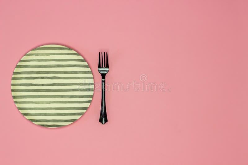 Плита и вилка на розовой предпосылке minimalism стоковая фотография rf