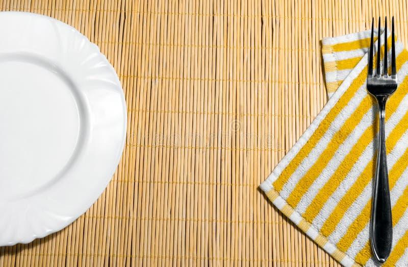 Плита и вилка на салфетке на таблице стоковые изображения