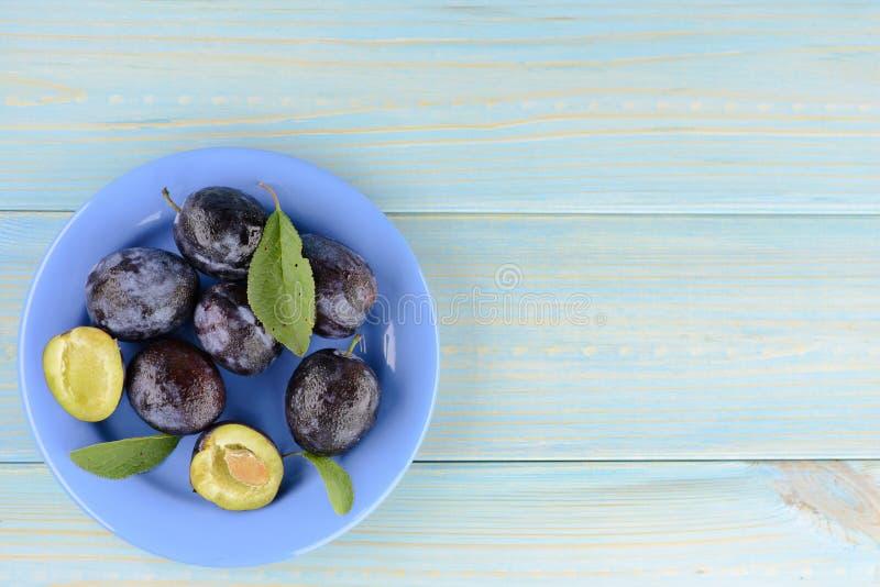 Плита очень вкусной зрелой сливы на голубом деревянном столе стоковая фотография rf