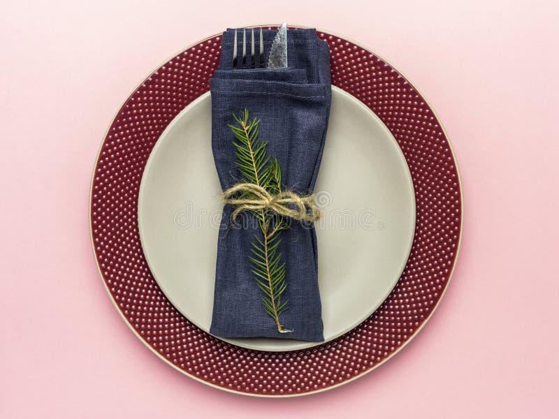 Плита сервировки праздника с вилкой и нож на розовой предпосылке стоковое изображение