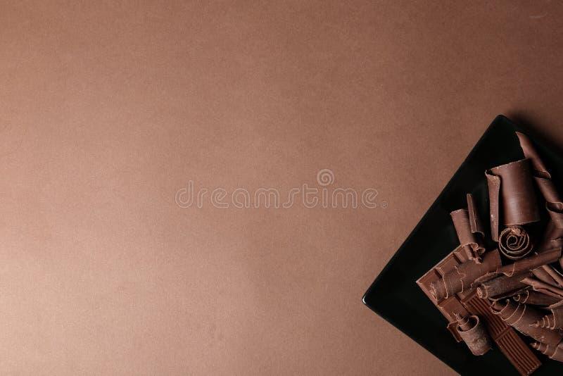 Плита со скручиваемостями и частями шоколада на предпосылке цвета стоковые фотографии rf